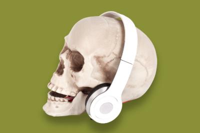 plastic skull wearing headphones on a green background