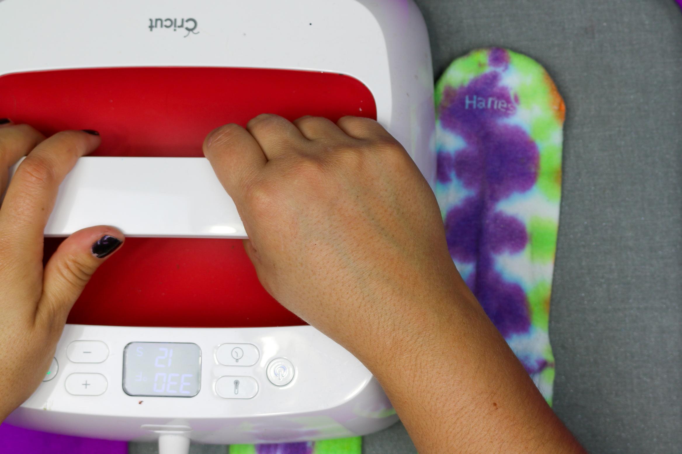 hands pressing an EasyPress onto tie dye socks