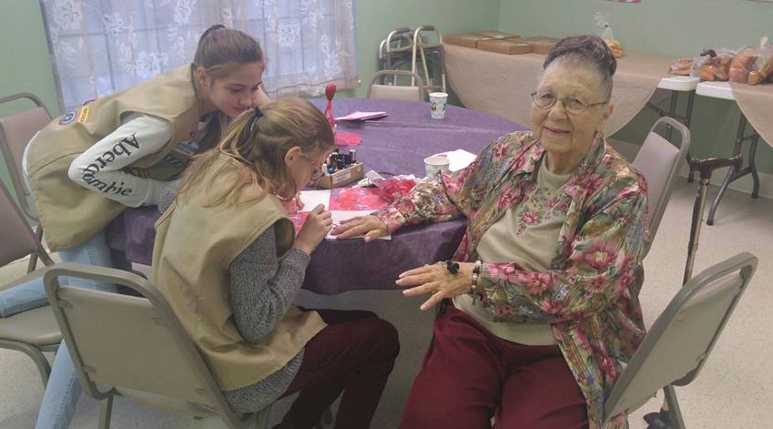 Girl Scouts give manicures at the retirement center.