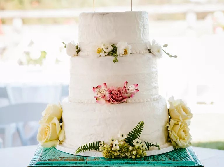 7 Beautiful Buttercream Frosted Wedding Cakes White textured buttercream wedding cake with garden topper