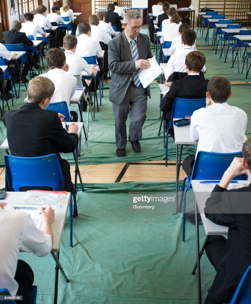 An exam invigilator hands out question papers before a GCSE Pictures     An exam invigilator hands out question papers before a GCSE exam at  Maidstone Grammar school