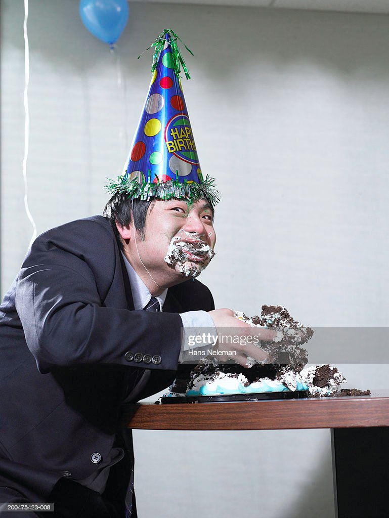 Businessman Eating Birthday Cake With Hands Stuffing Face