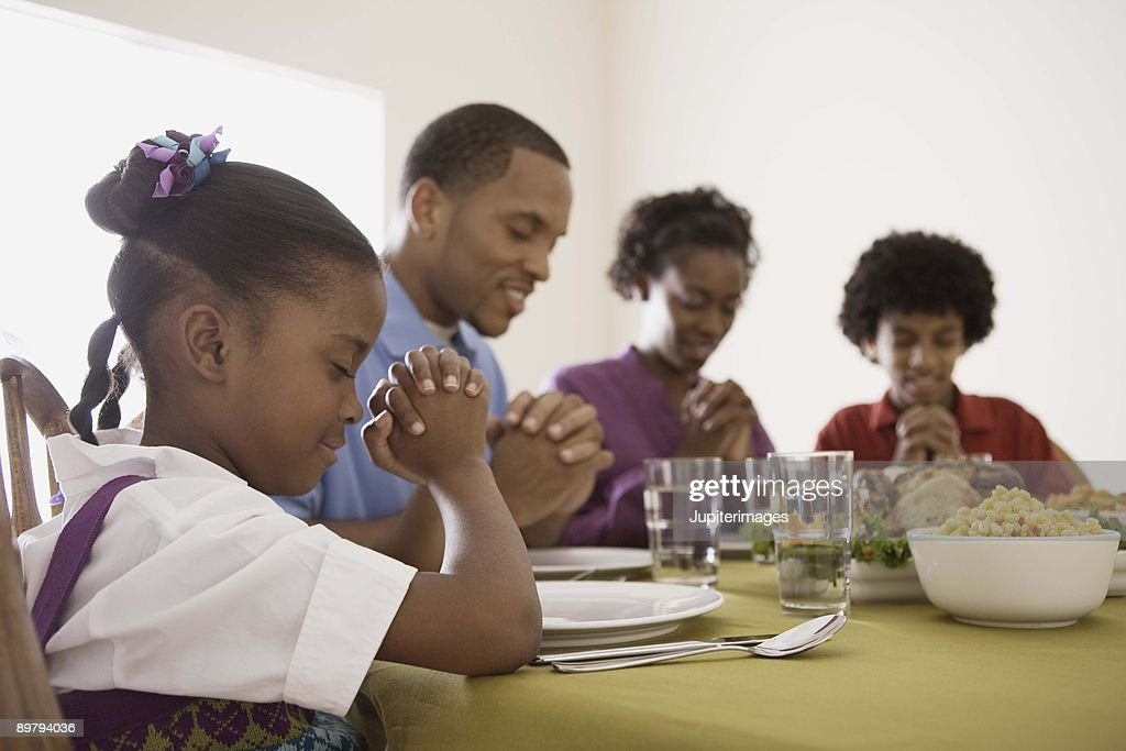 Family Praying Over Food At Dinner Table Stock Photo ...