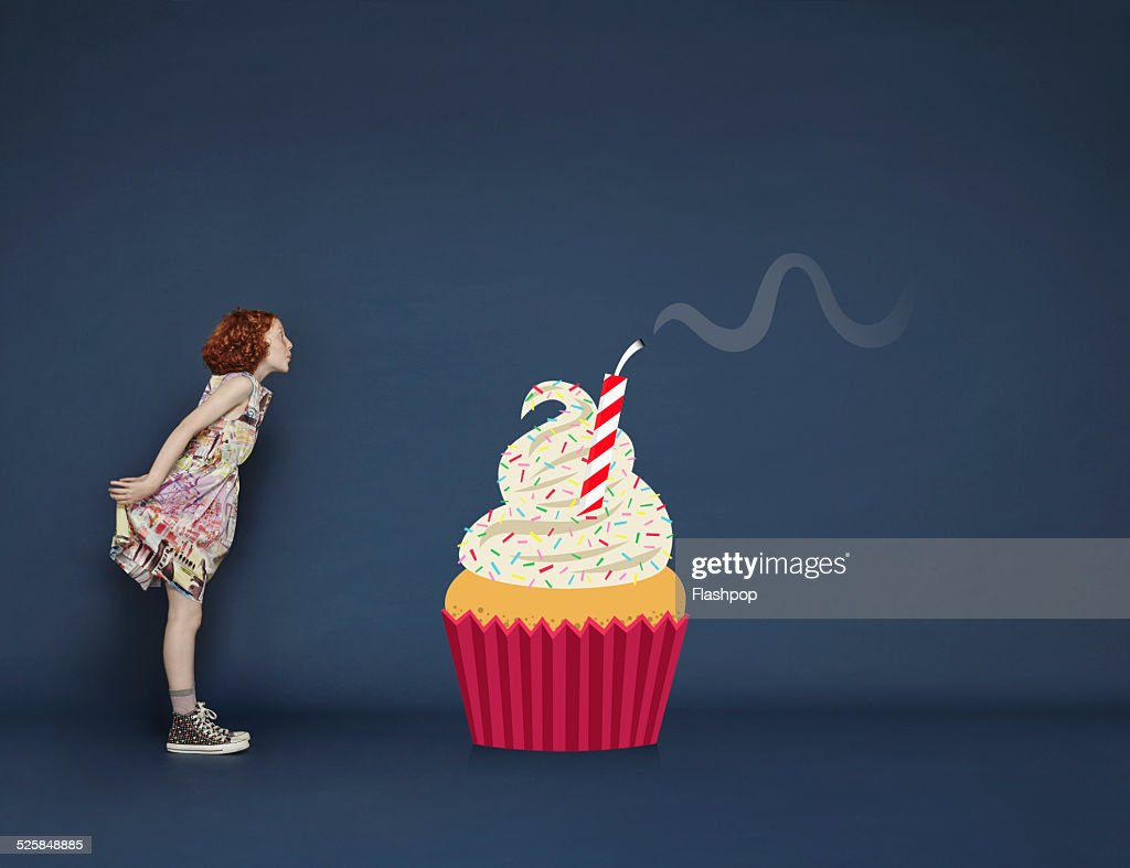 Girl Blowing Out Candles On Cartoon Birthday Cake Foto De