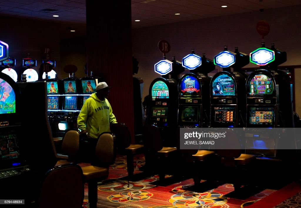 A Man Walks Past Slot Machines At A Near Empty Part Of A
