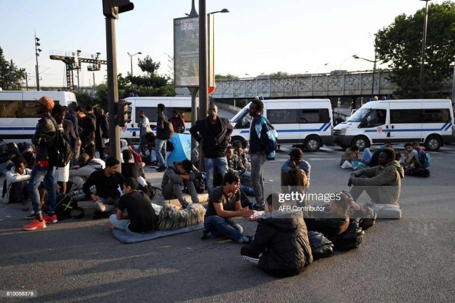 Migrants and refugees sit on the ground by vehicles of the French     Migrants and refugees sit on the ground by vehicles of the French anti riot  police during the evacuation of a makeshift camp at Porte de la Chapelle