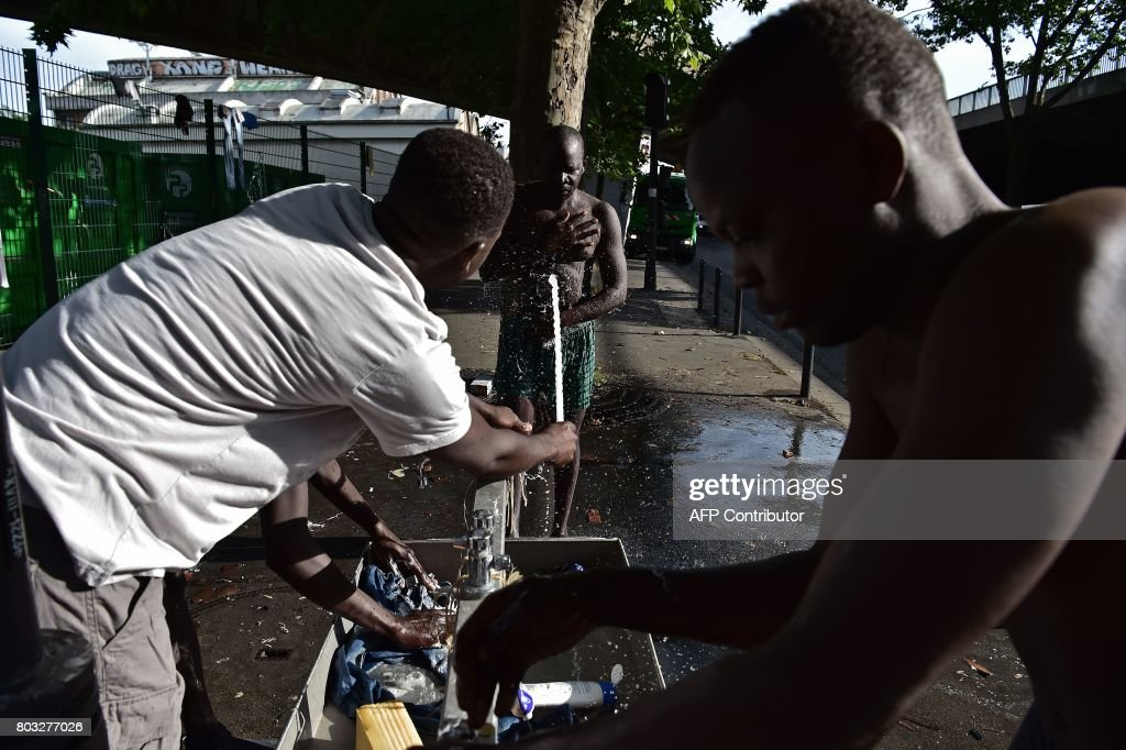 Migrants wash up on the pavement at Porte de la Chapelle in Paris on     Migrants wash up on the pavement at Porte de la Chapelle in Paris on June  29  2017  Some 1 200 people live on the street near the humanitarian centre  for