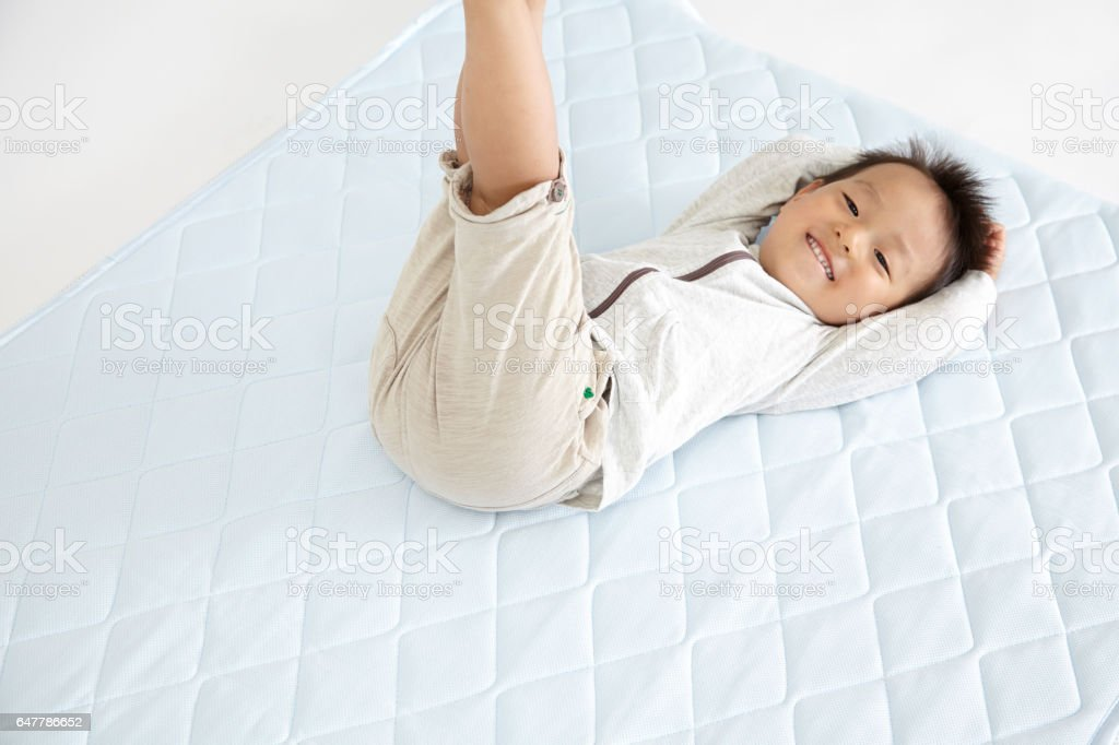 Baby Japanese Lie On The Mattress Man Stock Photo   More Pictures of     Baby Japanese lie on the mattress man royalty free stock photo