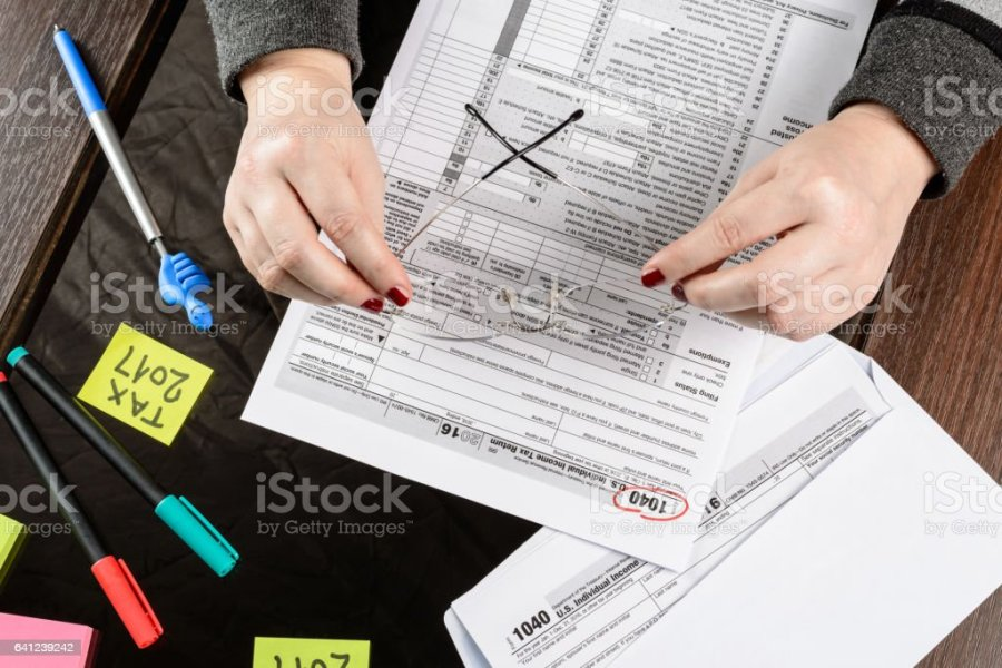 Woman Fills The Tax Form Working With Tax Documentsform 1040     Woman fills the tax form  working with tax documents Form 1040 Individual  Income Tax