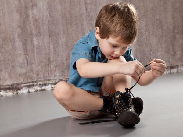 O próprio menino amarra os cadarços em sapatos