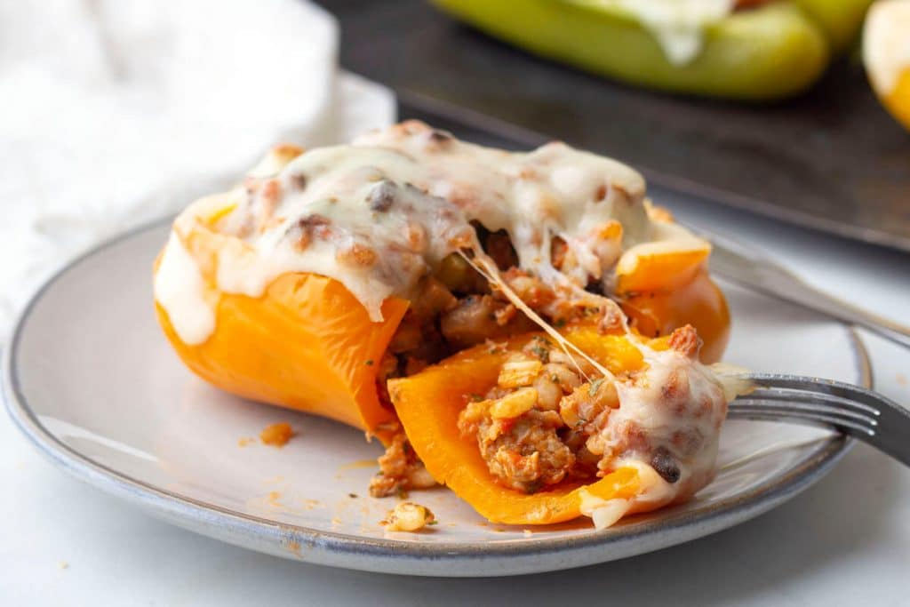 Stuffed orange bell peppers with ground turkey and barley with melted cheese on top