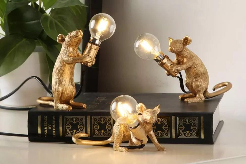 Garlands dengan gambar tikus terlihat sangat asli. Ini menahan bola lampu dalam cakar mereka.