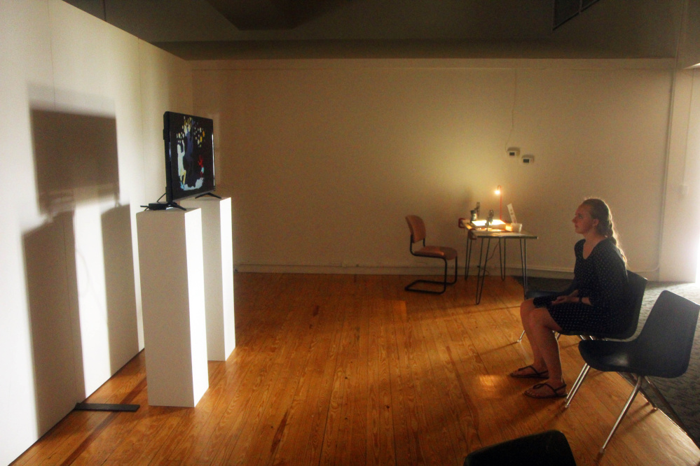 Waterville art show exhibit aims to challenge way we look at  listen     Common Street Arts  intern Alyssa Chesney watches a film by Kerry Laitala  on Sunday in