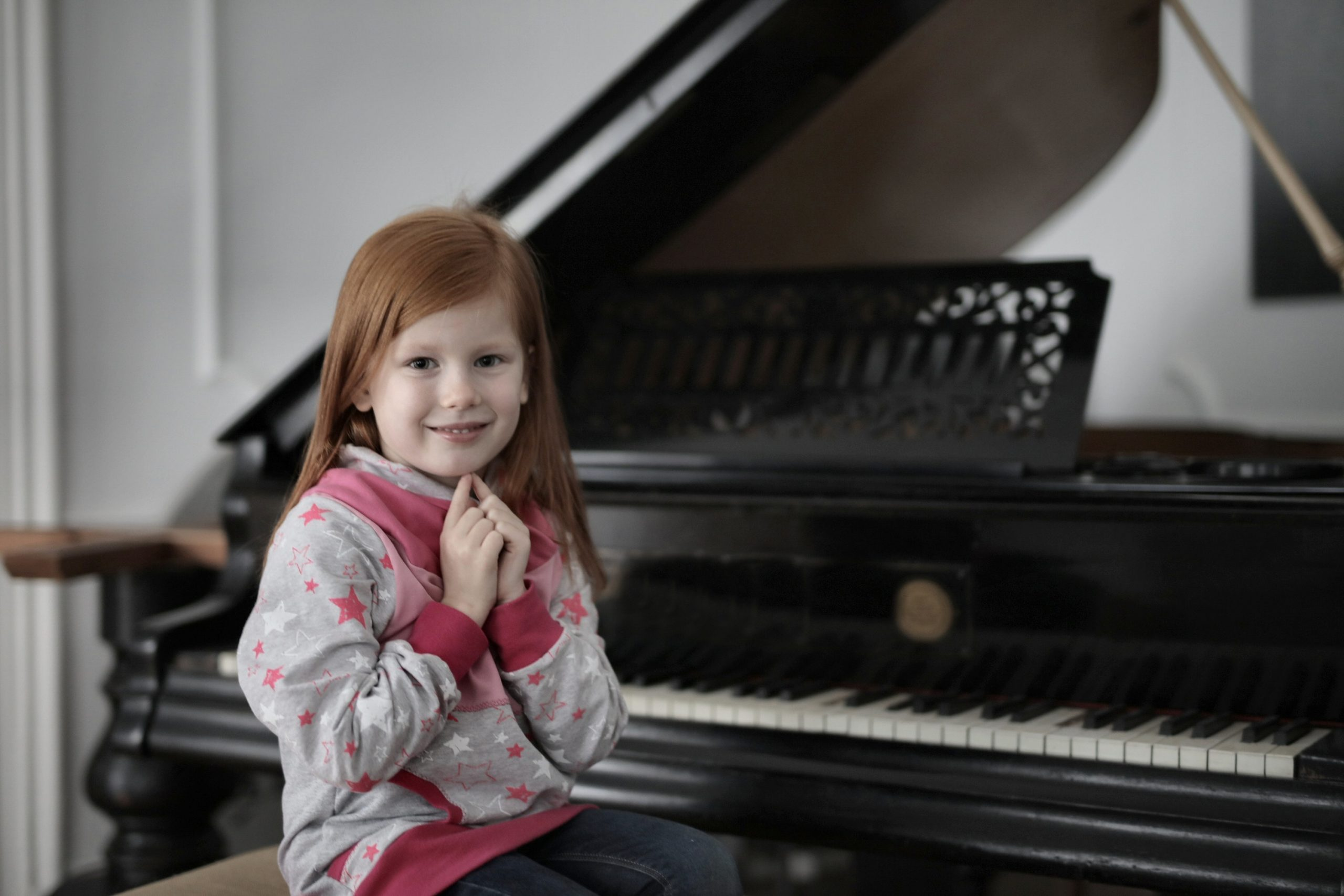 girl sitting in front of piano