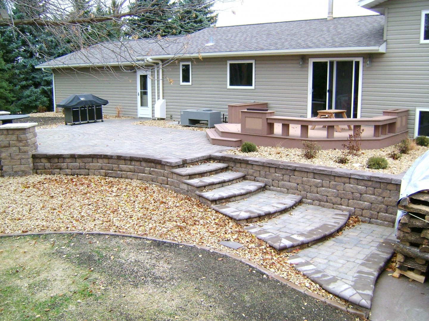 Raised Paver Patio With Retaining Walls Stairs Deck And Seating   Patio With Stairs From House   Concrete Slab   Simple   Back Yard   Composite Decking   Main Entrance Stamped Concrete Front