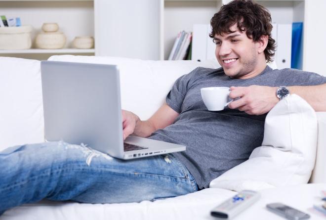 Guy tersenyum membaca laptop