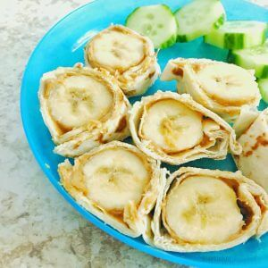 banana sliced with peanut butter wrapped in tortilla on a plate with sliced cucumber