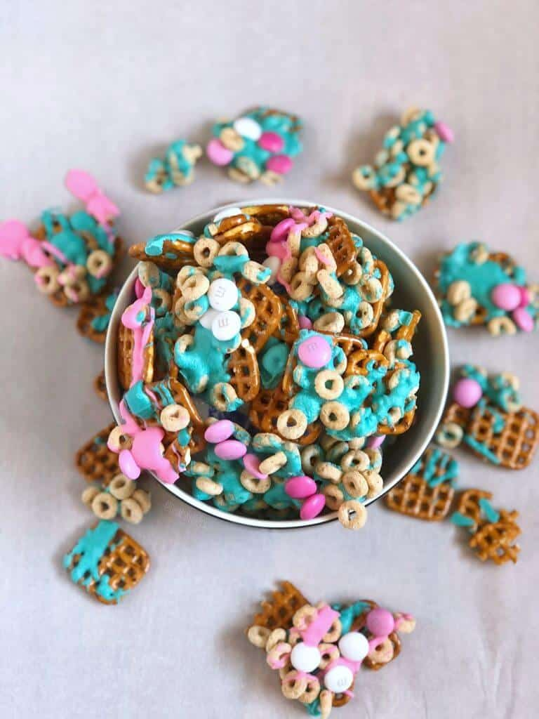 Trolls party snack mix for a birthday aprty is full of pretzels, cheerios, chocolate pieces and colorful melted turquoise and pink chocolate melts.