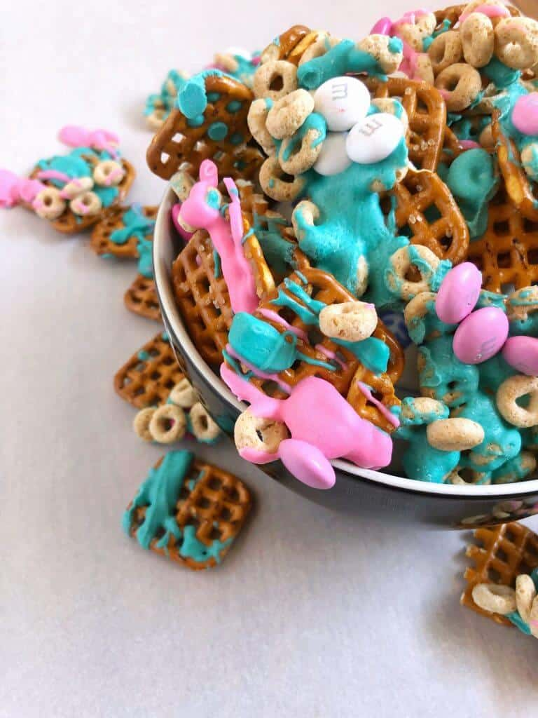 Overhead bowl of snack mix of pink and turquoise chocolate, pretzels and cereal