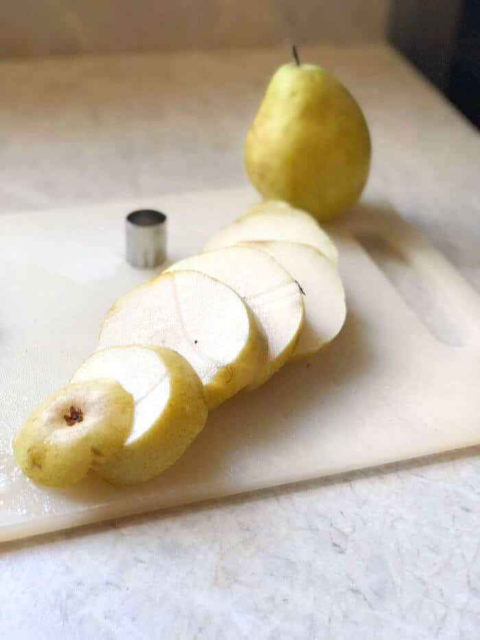 A pear on a cutting board cut into round slices