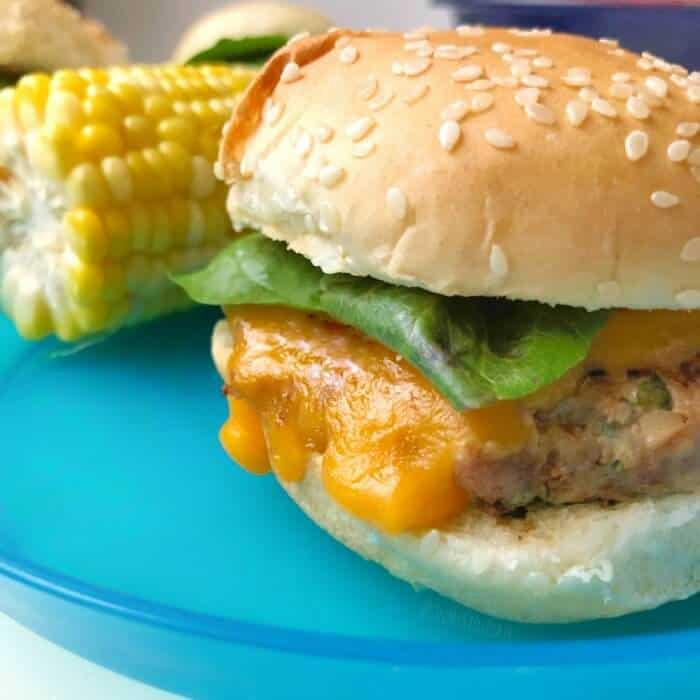 A close up of a turkey burger slider from the side with corn in the background