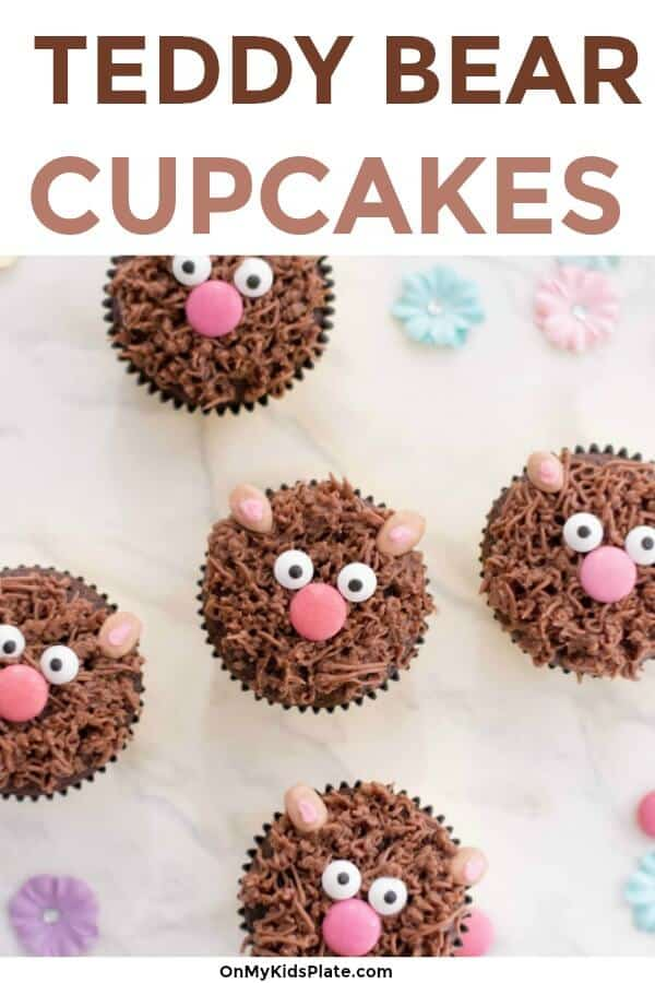 Five adorable brown bear cupcakes sit on a table with candy eyes, chocolate noses, candy ears and chocollae frosting.