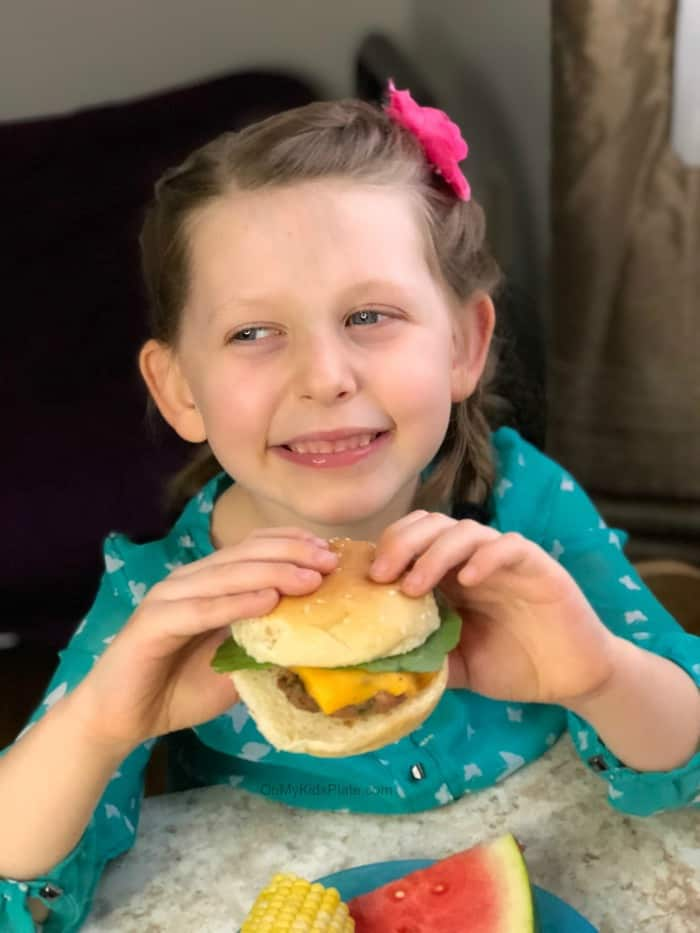 Little girl holds a turkey burger slider with cheese with both hands while smiling.
