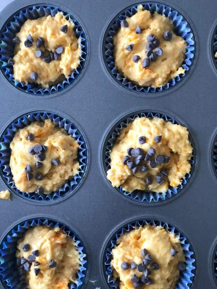 Muffin batter in a muffin tin topped with chocolate chips