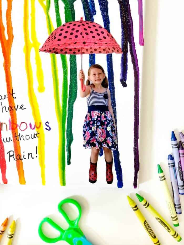 a close up of a child holding an umbrella on a canvas