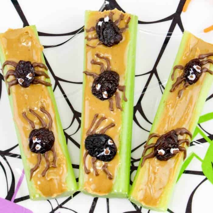Three peanut Butter celery snack topped with raisins made to look like spiders
