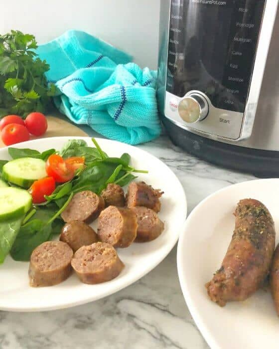 Two plates with sausage, one with salad also and an instant pot in the background