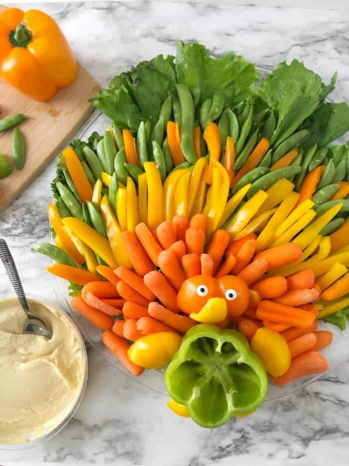 A closer view of a platter of vegetables made to look like a turkey with a container of hummus next to the platter