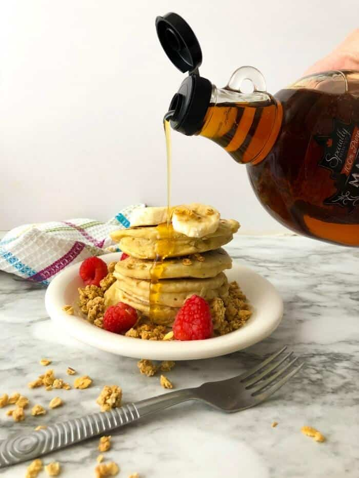 Syrup being poured on a stack of almond milk pancakes