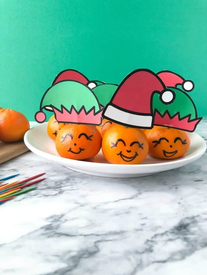 A bunch of clementines on a plate all wearing santa and elf hats with faces drawn on. Toothpicks and another clementine sit next to them