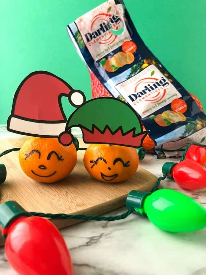 Clementines with faces drawn on and wearing paper santa and elf hats next to a bag of clementines