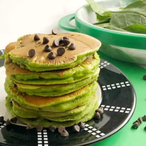 A stack of green spinach pancakes sits on a plate with a sprinkle of chocolate chips on top.