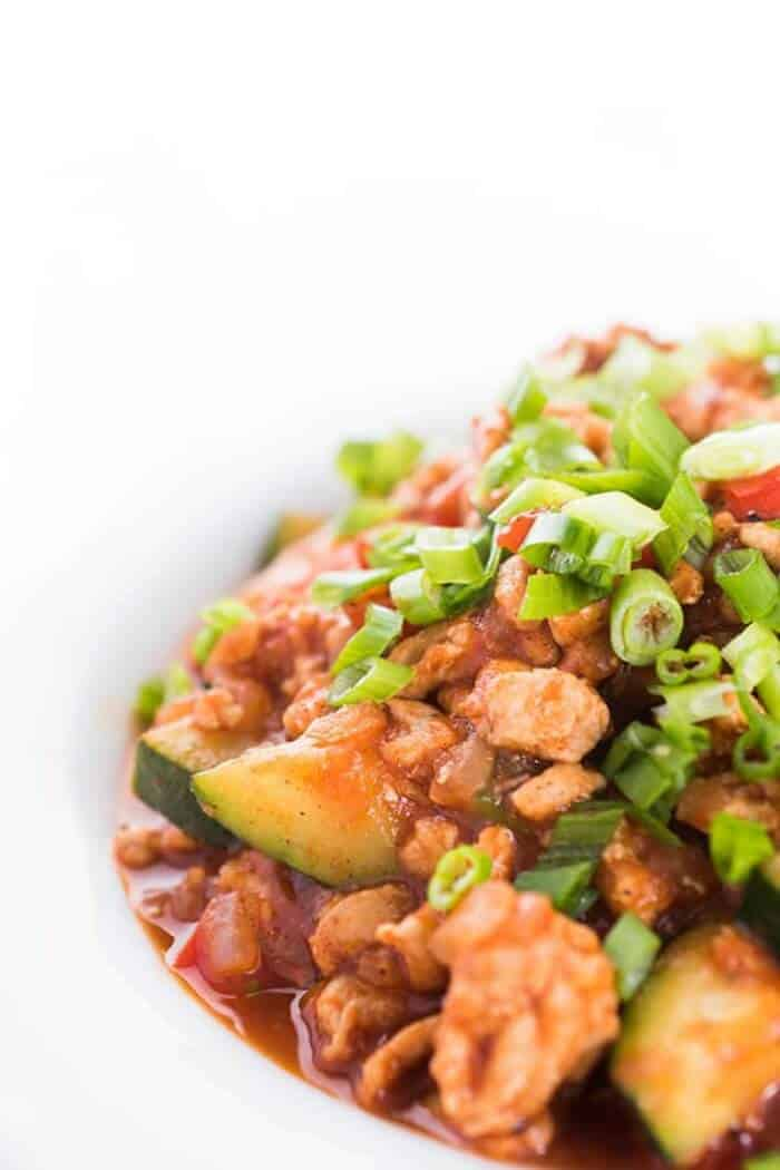 A close up of ground turkey, green onions and zucchini cooked in a red sauce