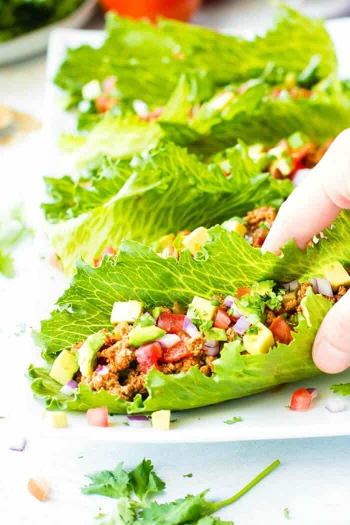 Several pieces of lettuce filled with taco ingredients.