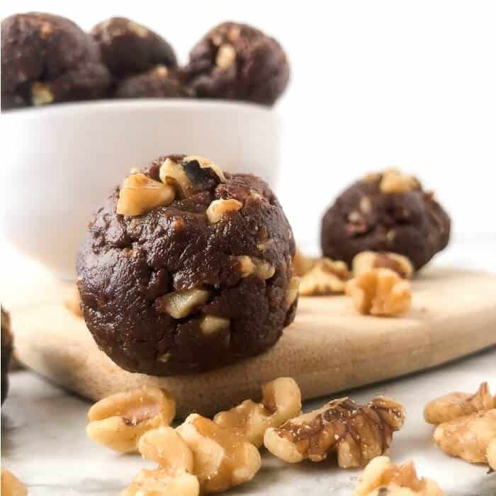 Chocolate walnut energy bite in front of a bowl of energy bites sitting next to walnuts.