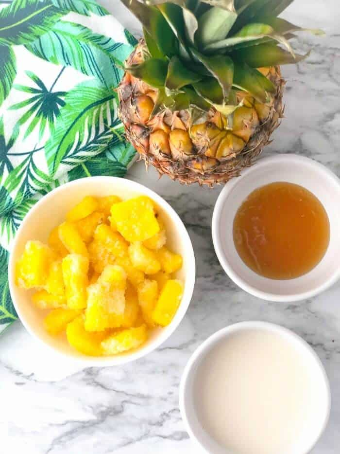 Frozen pineapple sliced, almond milk, honey in bowls and fresh pineapple from overhead.