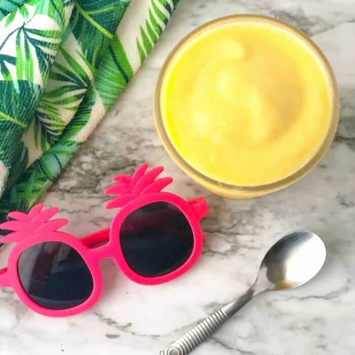 A pineapple dole whip smoothie form overhead next to kids' sunglasses, a towel and a spoon.