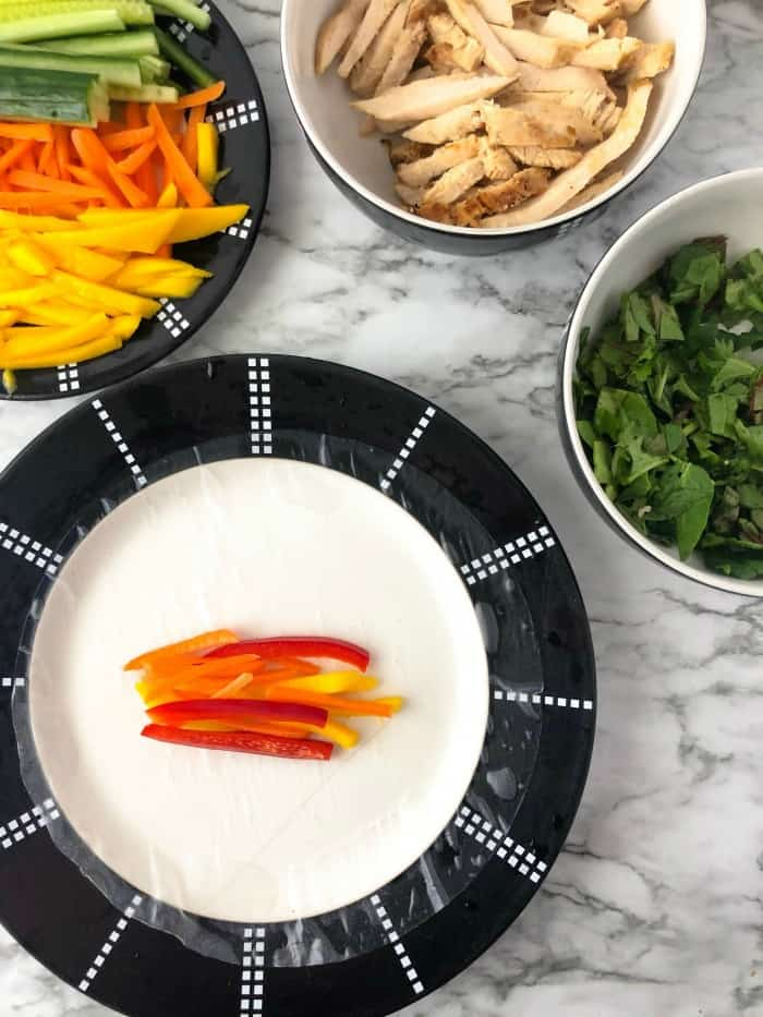 A spring roll rice wrapper on a plate with peppers in the middle, other chopped ingredients in bowls next to the plate