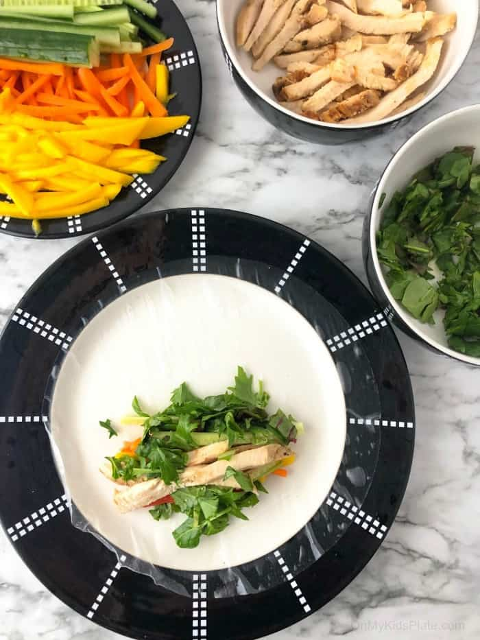 A fresh spring roll wrapper on a plate with chicken and greens in the roll, other ingredients in bowls next to the plate.