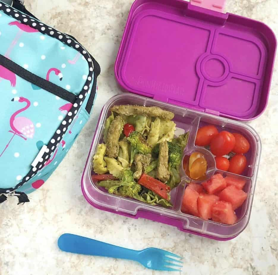 A kid\'s bento lunchbox filled with pesto pasta with chicken, tomatoes and gummies next to an insulated lunchbox and a blue fork