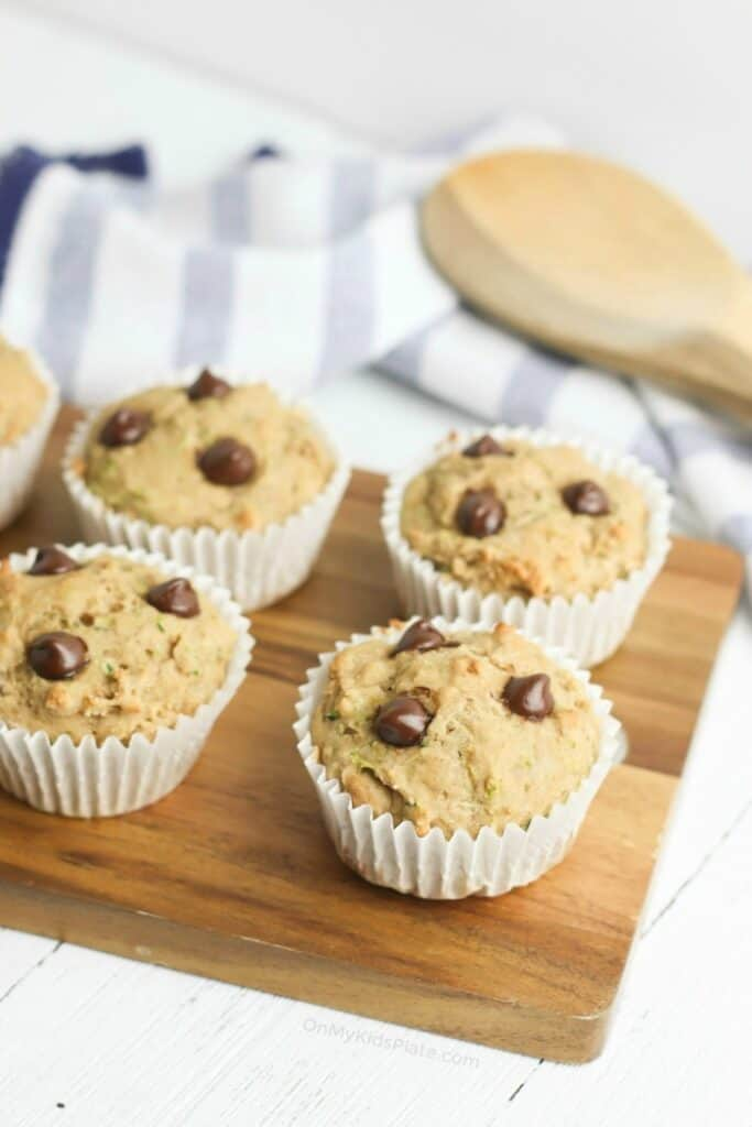 Four muffins with chocolate chips on a cutting board, a wooden spoon and towel behind