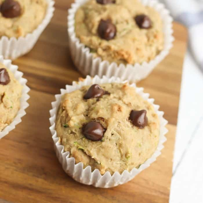 Several muffins with chocolate chips on a cutting board