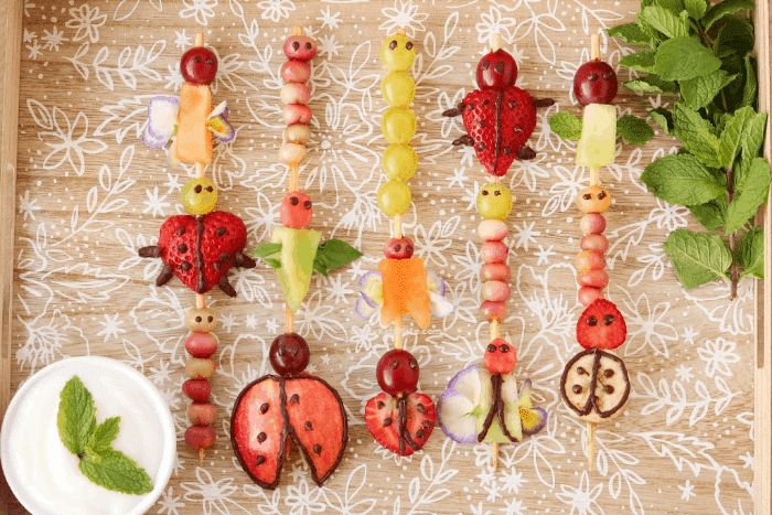 Five fruit skewers decorated like ladybugs, caterpillars and other insects.