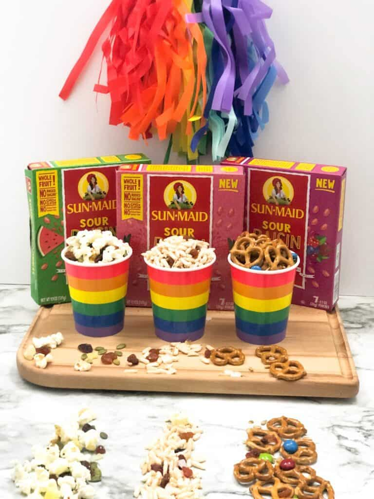Three different rainbow cups of different trail mixes on a cutting board next to three boxes of flavored raisins