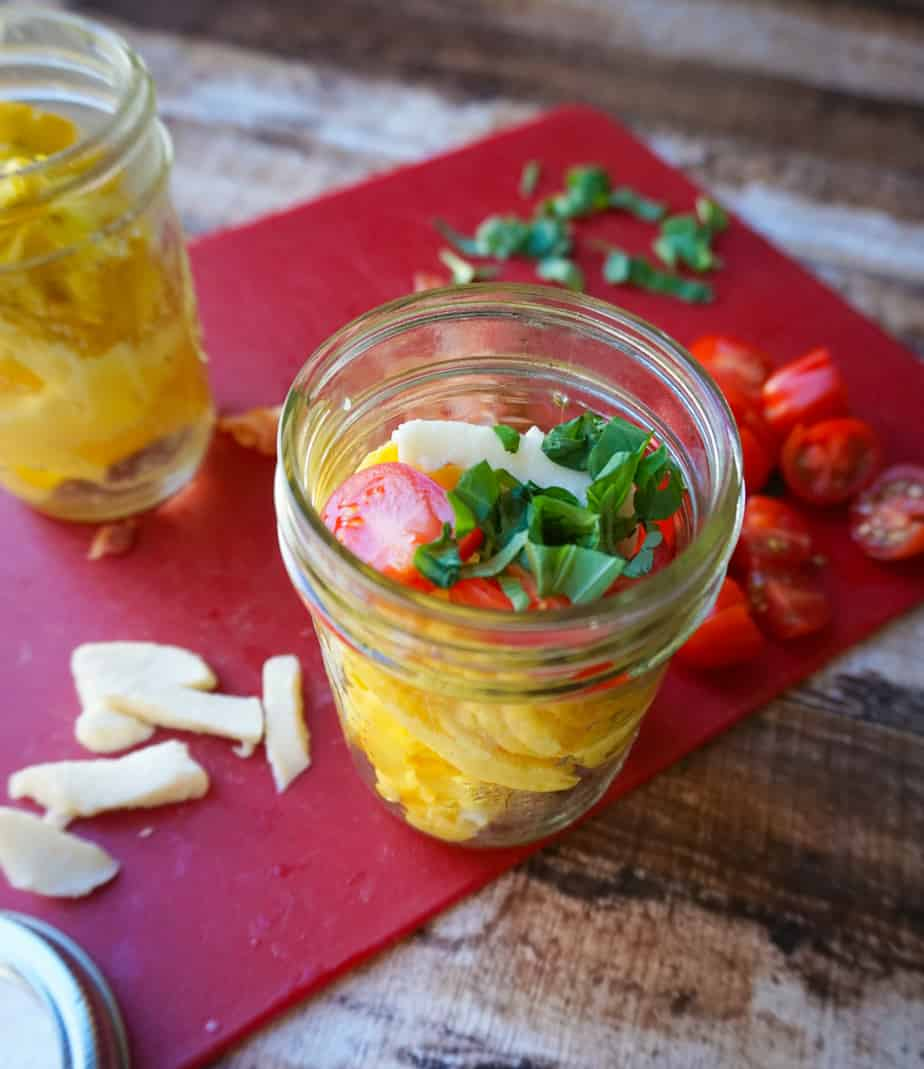 Eggs in a small mason jar topped with tomato, basil and cheese