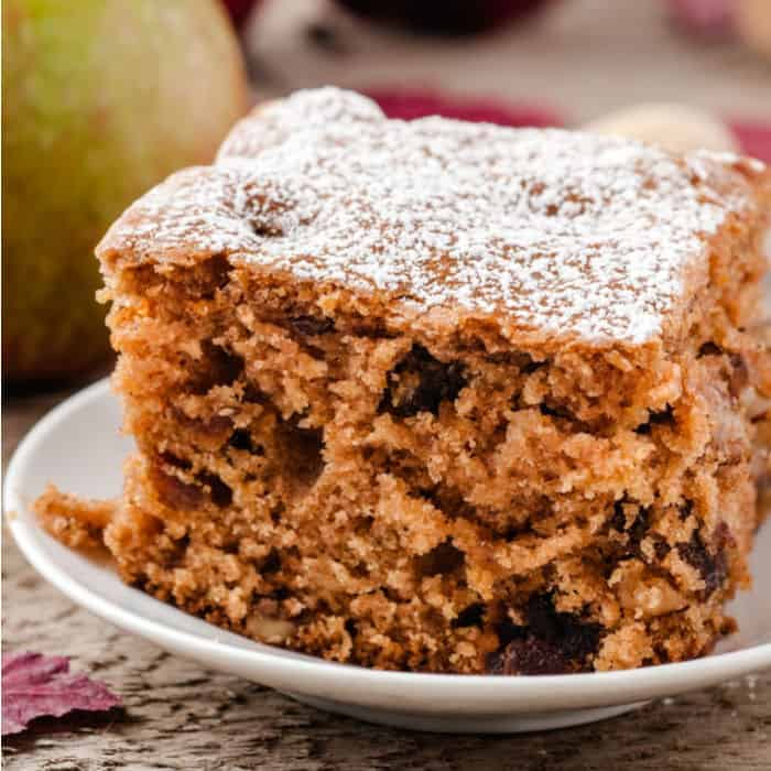 A slice of apple walnut cake sits on a plate with an apple in the background.